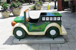Sculpture of small car in downtown Elmhurst painted with golf course diagrams