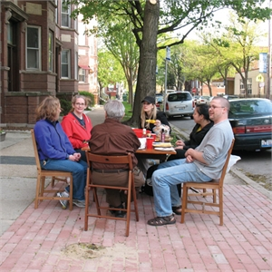 Neighbors eating lunch at table on sidewalk